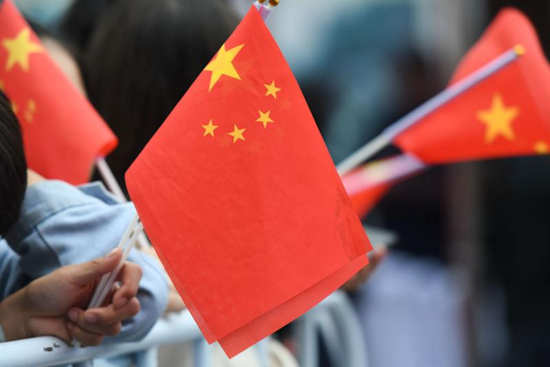Pictured are people holding small China flags.
