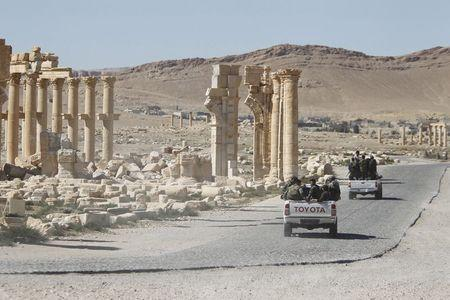 Syrian army soldiers drive past the Arch of Triumph in the historic city of Palmyra, in Homs Governorate, Syria in this April 1, 2016 file photo. REUTERS/Omar Sanadiki/Files
