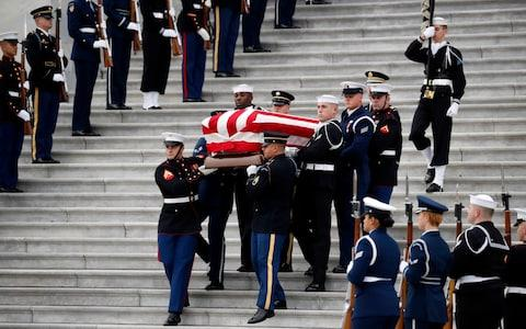 The flag-draped casket of former President George HW Bush is carried by a joint services military honor guard - Credit: AP