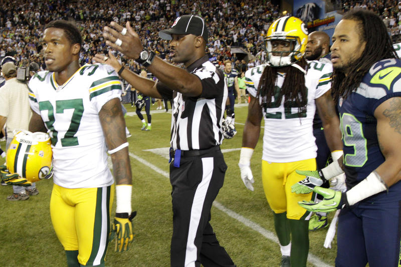 An official gestures as Green Bay Packers cornerback Sam Shields (37), safety Jerron McMillian (22) and Seattle Seahawks free safety Earl Thomas (29) leave the field in the second half of an NFL football game, Monday, Sept. 24, 2012, in Seattle. After a period of confusion, a Seahawks touchdown by wide receiver Golden Tate was allowed to stand for the 14-12 win. (AP Photo/Ted S. Warren)