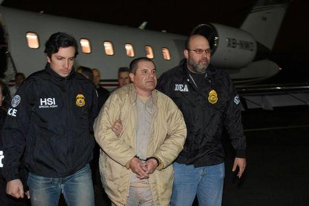 """FILE PHOTO: Mexico's top drug lord Joaquin """"El Chapo"""" Guzman is escorted as he arrives at Long Island MacArthur airport in New York"""
