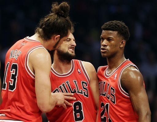 Chicago Bulls guard Marco Belinelli, center, reacts as teammates Joakim Noah, left, and Jimmy Butler talk to him during the first half in Game 7 of their first-round NBA basketball playoff series against the Brooklyn Nets in New York, Saturday, May 4, 2013. (AP Photo/Julio Cortez)