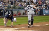 Milwaukee Brewers' Mike Moustakas scores from first past San Diego Padres catcher Austin Hedges on an RBI double by Ryan Braun during the first inning of a baseball game Thursday, Sept. 19, 2019, in Milwaukee. (AP Photo/Morry Gash)