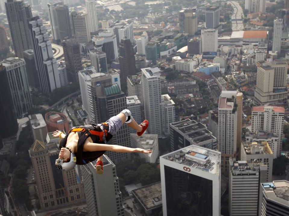 France's base jumper Florian Pays gestures while leaping from Malaysia's landmark KL Tower, the 421-meter (1,389-foot) broadcasting tower in downtown Kuala Lumpur, Malaysia, Saturday, Sept. 29, 2012. (AP Photo/ Vincent Thian)