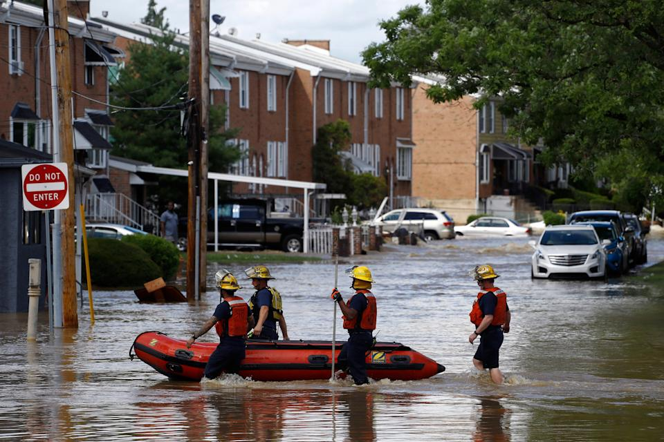 Philadelphia firefighters walk through a flooded neighborhood after Tropical Storm Isaias moved through, Tuesday, Aug. 4, 2020, in Philadelphia. The storm spawned tornadoes and dumped rain during an inland march up the U.S. East Coast after making landfall as a hurricane along the North Carolina coast. (AP Photo/Matt Slocum)