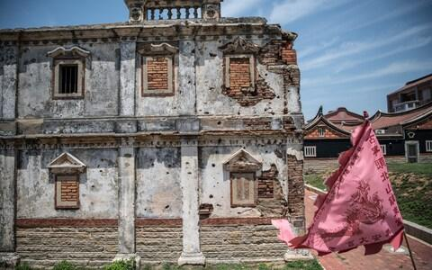 An old Western style house still bears bullet holes and damage from the Battle of Guningtou, an attempted invasion of Kinmen by Communist forces in 1949 - Credit: Carl Court/Getty