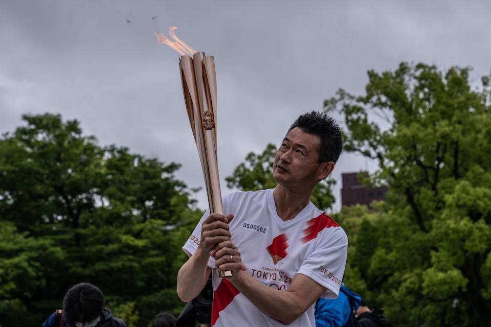 A Tokyo 2020 Olympics torch bearer pauses during a relay in the Hiroshima Peace Park in Hiroshima, Japan.