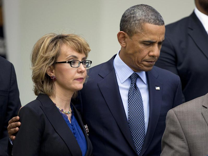 FILE - In this April 17, 2013 file photo, President Barack Obama puts his arm around former Arizona Rep. Gabrielle Giffords before speaking in the Rose Garden at the White House in Washington about measures to reduce gun violence. Striving to take action where Congress would not, the Obama administration announced new steps Thursday on gun control, curbing the import of military surplus weapons and proposing to close a little-known loophole that lets felons and others circumvent background checks by registering guns to corporations. (AP Photo/Manuel Balce Ceneta, File)