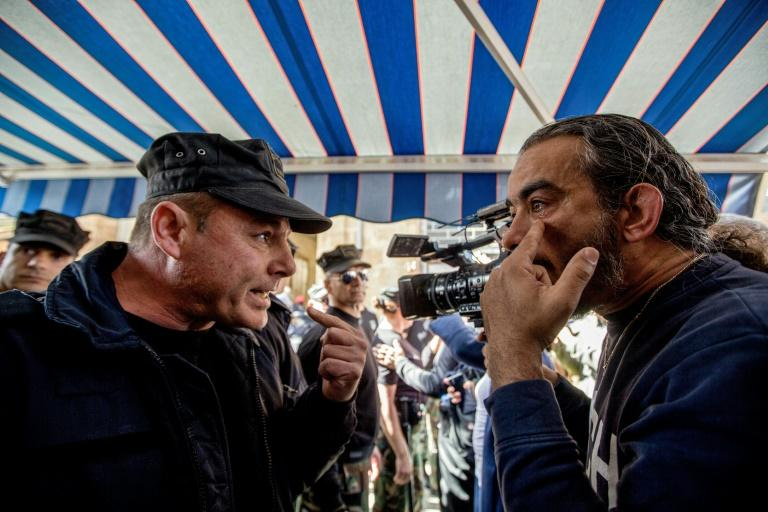 A cameraman speaks with a Cyprus police officer during the protest in the divided capital Nicosia
