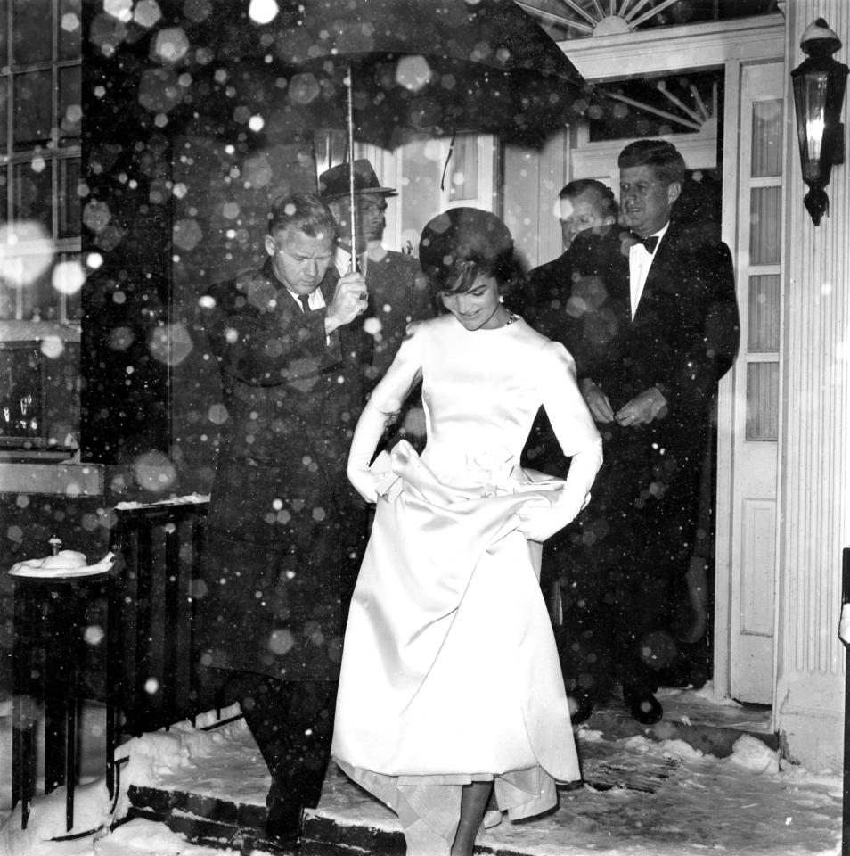 Jacqueline Kennedy lifts the skirt of her inaugural ball gown as she and her husband, President-elect John F. Kennedy, leave their Georgetown home in the snowfall en route to the inaugural concert in Washington, D.C., Jan. 19, 1961.  (AP Photo)