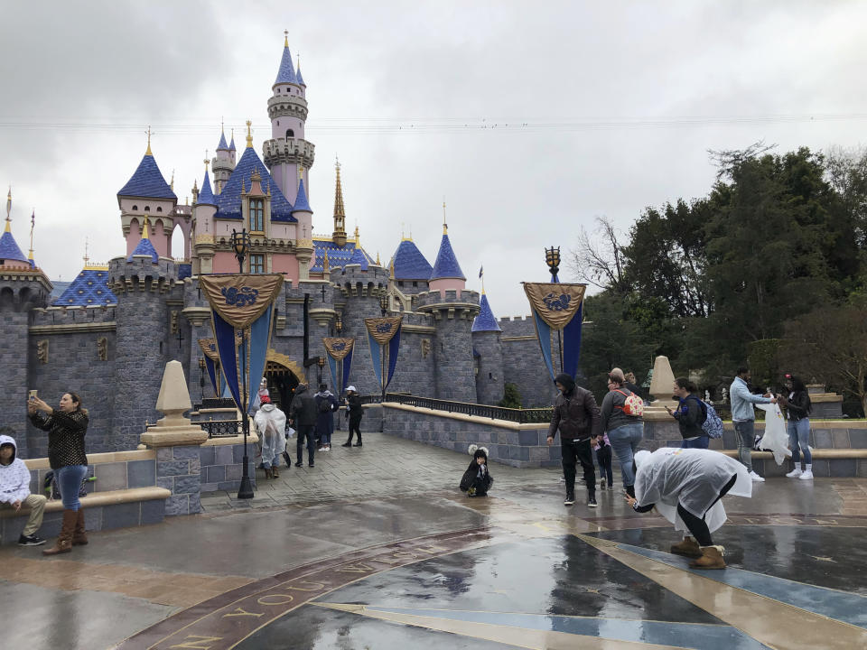 FILE - In this March 13, 2020, file photo, visitors take photos at Disneyland in Anaheim, Calif. Disney is proposing to reopen its Southern California theme parks in mid-July after a four-month closure due to the coronavirus, the company said on Wednesday, June 10, 2020. Disney is postponing the mid-July reopening of its Southern California theme parks until it receives guidelines from the state. The company announced Wednesday, June 23, 2020, an indefinite postponement for Disneyland and Disney California Adventure in Anaheim. (AP Photo/Amy Taxin, File)