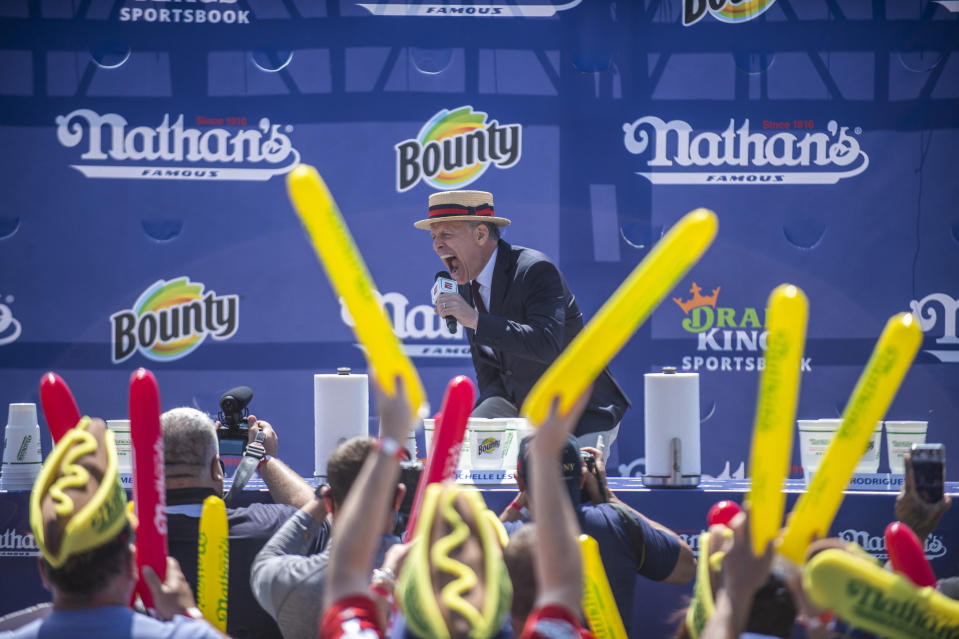 George Shea, the event's host, livens up the crowd at the Nathan's Famous Fourth of July International Hot Dog-Eating Contest in Coney Island's Maimonides Park on Sunday, July 4, 2021, in New York. (AP Photo/Brittainy Newman)