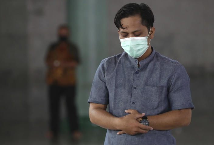 A man wearing mask to help curb the spread of coronavirus outbreak prays at a mosque in Tangerang, Indonesia, Tuesday, Jan. 26, 2021. Indonesia has reported more cases of the virus than any other countries in Southeast Asia. (AP Photo/Tatan Syuflana)