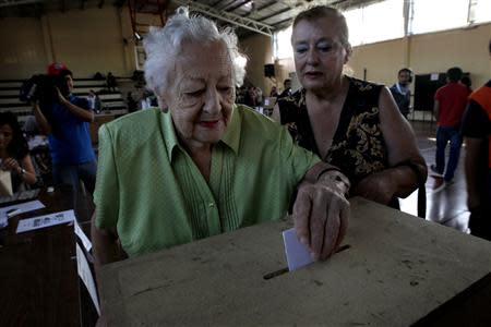 A woman casts her vote at a polling station during the presidential election in Santiago, December 15, 2013. REUTERS/Ivan Alvarado