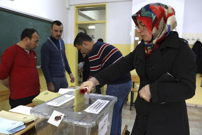 A woman cast her ballots at a polling station during the municipal elections in Ankara, Turkey, Sunday, March 31, 2019. Turkish citizens have begun casting votes in municipal elections for mayors, local assembly representatives and neighborhood or village administrators that are seen as a barometer of Erdogan's popularity amid a sharp economic downturn. (AP Photo/Ali Unal)
