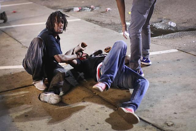 <p>A man gets help after being overcome by tear gas that police launched at demonstrators protesting the killing of teenager Michael Brown on August 17, 2014 in Ferguson, Missouri. Police shot smoke and tear gas into the crowd of several hundred as they advanced near the police command center which has been set up in a shopping mall parking lot. Brown was shot and killed by a Ferguson police officer on August 9. Despite the Brown family's continued call for peaceful demonstrations, violent protests have erupted nearly every night in Ferguson since his death. (Scott Olson/Getty Images) </p>