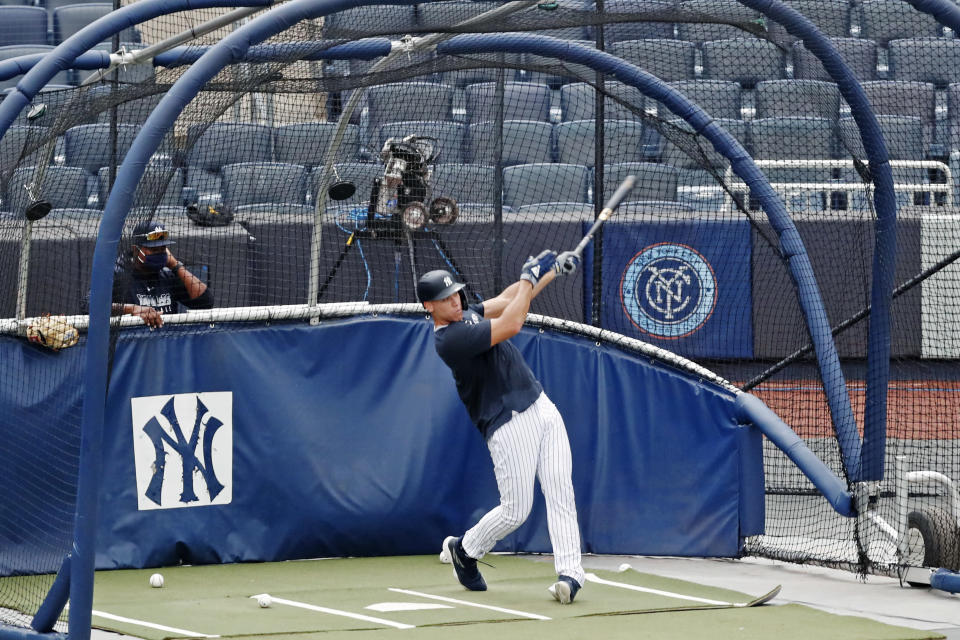 New York Yankees hitting coach Marcus Thames, left, watches Aaron Judge take batting practice during a baseball summer training camp workout, Wednesday, July 8, 2020, at Yankee Stadium in New York. (AP Photo/Kathy Willens)