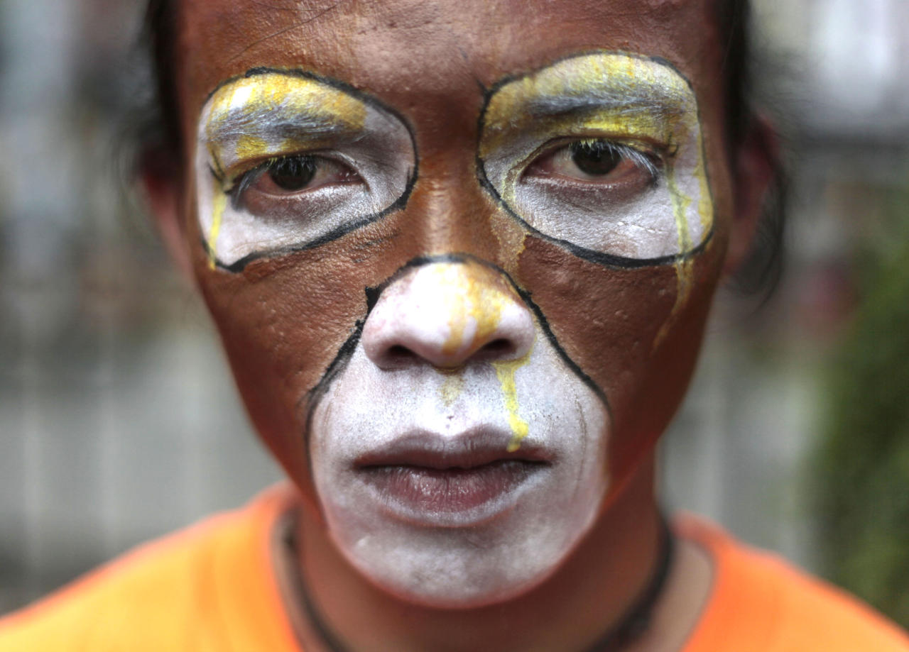 An activist of the Center for Orangutan Protection has his face painted as orangutan during a protest demanding improvement of orangutans' welfare by the government at Jakarta's Ragunan Zoo outside the governor's office in Jakarta, Indonesia, Thursday, Aug. 4, 2011. The activists said that the zoo did not provide decent living environment for their orangutans causing them to fall into depression. Orangutan populations in Indonesia's Borneo and Sumatra islands are facing severe threats from habitat loss, illegal logging, fires and poaching. (AP Photo/Dita Alangkara)