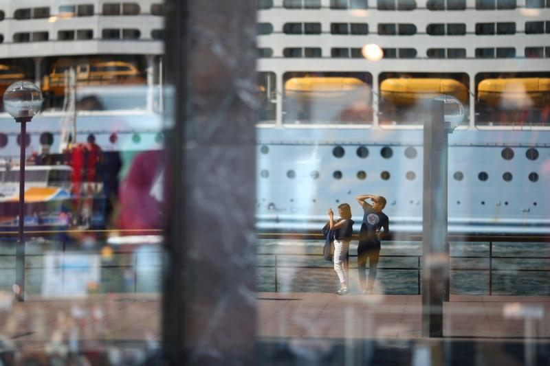 Two people, seen in the reflection of a shop window, stand on the mostly deserted waterfront of the Sydney Opera House in Sydney
