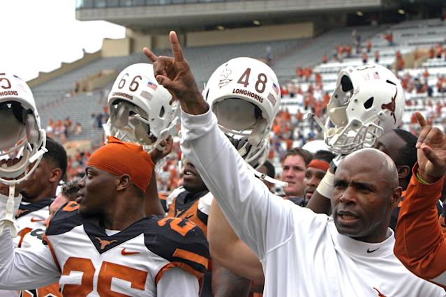 """Texas coach Charlie Strong gives the """"hook 'em horns"""" sign while his players raise their helmets after the Orange and White spring NCAA college football game, Saturday, April 19, 2014, in Austin, Texas. (AP Photo/Michael Thomas)"""