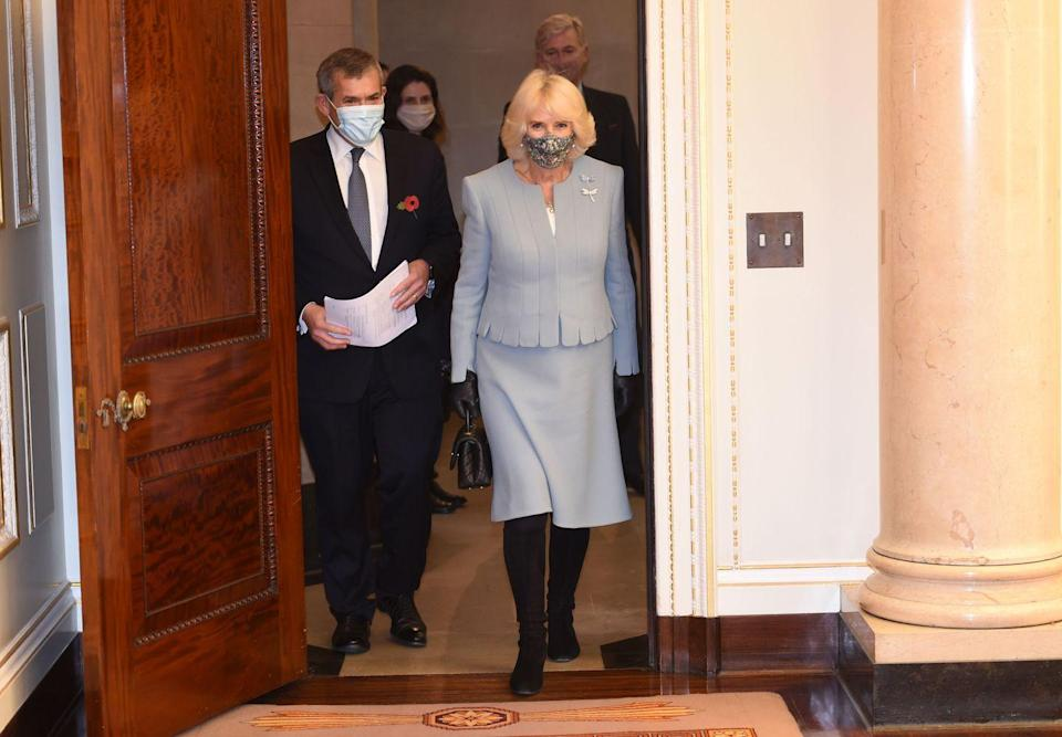 <p>The Duchess of Cornwall wore a powder blue suit, knee high boots, and dragonfly pins to visit the headquarters of the Bank of England in London. She paired the look with a floral protective mask. </p>