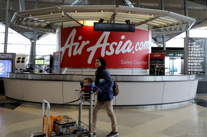 A woman walks past an AirAsia counter at Kuala Lumpur International Airport in Sepang