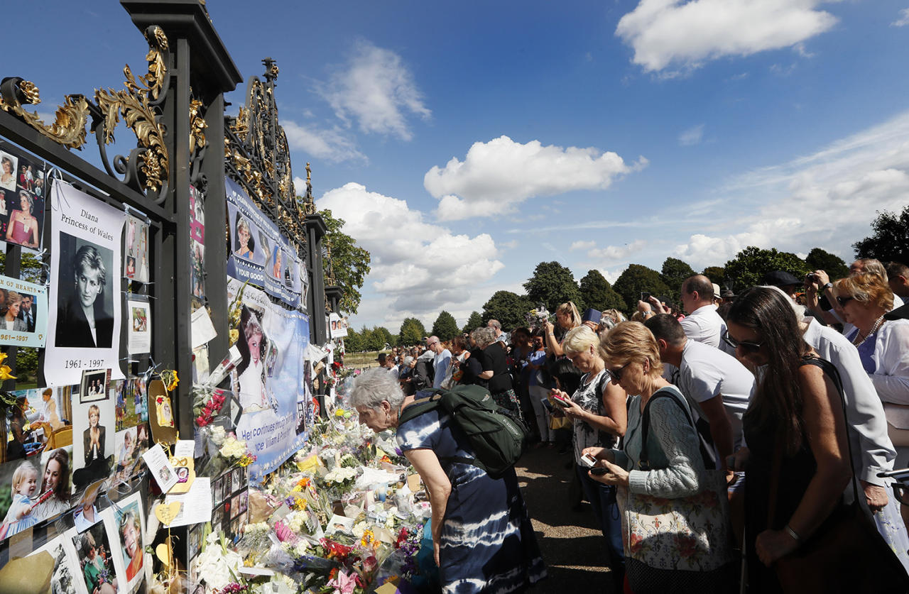 <p>People crowd around the gates of Kensington Palace in London to pay tribute to the late Diana, Princess of Wales, Aug. 31, 2017. (Photo: Kirsty Wigglesworth/AP) </p>
