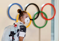 A German athlete, wearing face mask, walks past the Olympic rings display on their arrival at Haneda airport in Tokyo, Thursday, July 1, 2021. The pressure of hosting an Olympics during a still-active pandemic is beginning to show in Japan. The games begin July 23, with organizers determined they will go on, even with a reduced number of spectators or possibly none at all.(Kyodo News via AP)