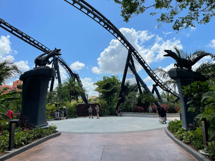 Two raptor statues on pedestals in front of the VelociCoaster