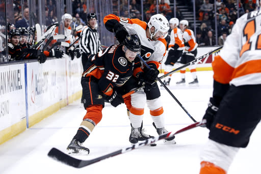 Anaheim Ducks defenseman Jacob Larsson (32) vies for the puck with Philadelphia Flyers forward Andy Andreoff (10) during the first period of an NHL hockey game Sunday, Dec. 29, 2019, in Anaheim, Calif. (AP Photo/Ringo H.W. Chiu)