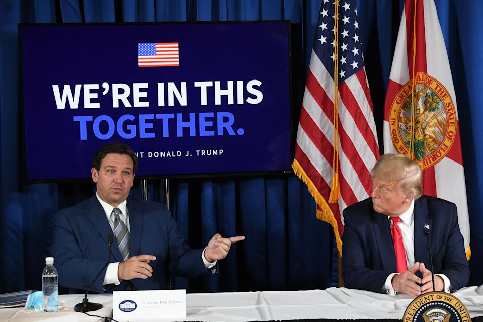 US President Donald Trump (R) and Florida's governor Ron DeSantis hold a COVID-19 and storm preparedness roundtable in Belleair, Florida, July 31, 2020. (Photo by SAUL LOEB / AFP) (Photo by SAUL LOEB/AFP via Getty Images)