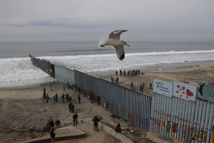 FILE - In this Dec. 10, 2018, file photo, people look on from the Mexican side, left, as U.S. Border Patrol agents on the other side of the U.S. border wall in San Diego prepare for the arrival of hundreds of pro-migration protestors, seen from Tijuana, Mexico. The southern border is nearly 2,000 miles long and already has about 650 miles of different types of barriers, including short vehicle barricades and tall, steel fences that go up to 30 feet high. (AP Photo/Rebecca Blackwell, File)