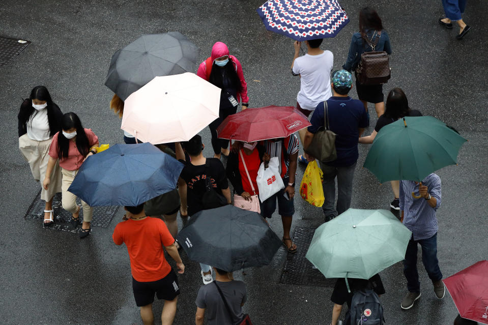 SINGAPORE - JANUARY 10: People wearing protective masks cross a street in the rain on January 10, 2021 in Singapore. As of January 10, the Ministry of Health confirmed 42 new imported COVID-19 cases, with zero cases in the wider community bringing the country's total to 58,907. (Photo by Suhaimi Abdullah/Getty Images)