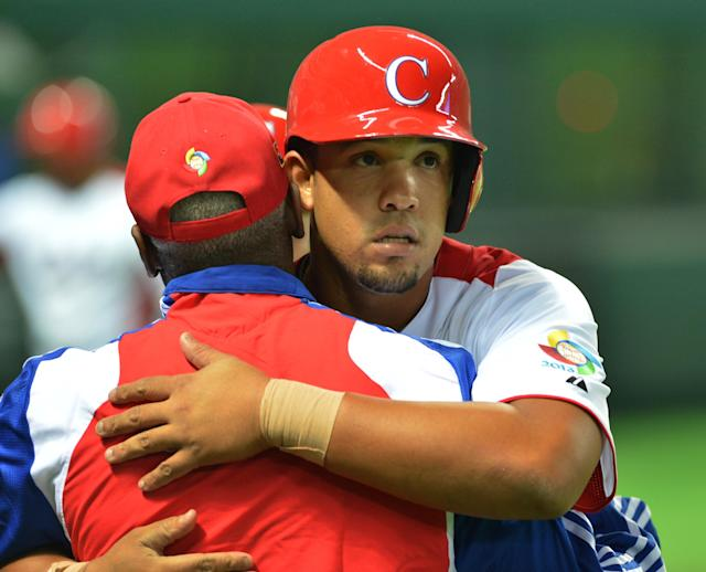 Cuba's Jose Abreu (R) celebrates with a coach after his grand slam against China during the fifth inning of their first-round Pool A game in the World Baseball Classic tournament in Fukuoka on March 4, 2013. AFP PHOTO / KAZUHIRO NOGIKAZUHIRO NOGI/AFP/Getty Images