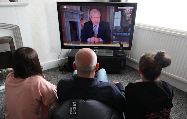 People in a house in Liverpool watch Prime Minister Boris Johnson addressing the nation about easing the coronavirus lockdown from Downing Street, London.
