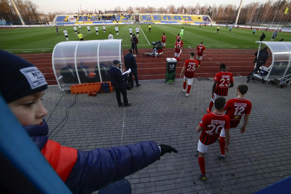 In this photo taken on Friday, March 27, 2020, a boy watches players as they enter the field prior to the Belarus Championship soccer match between Torpedo-BelAZ Zhodino and Belshina Bobruisk in the town of Zhodino, Belarus. Longtime Belarus President Alexander Lukashenko is proudly keeping soccer and hockey arenas open even though most sports around the world have shut down because of the coronavirus pandemic. The new coronavirus causes mild or moderate symptoms for most people, but for some, especially older adults and people with existing health problems, it can cause more severe illness or death. (AP Photo/Sergei Grits)