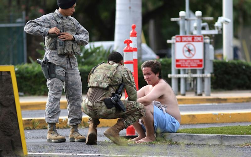 Security forces help a man outside the main gate of the base in Hawaii, where three people were shot by the gunman - AP