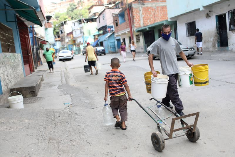 FILE PHOTO: People walk with plastic containers near an unknown water source in the low-income neighbourhood of Petare amid the coronavirus disease (COVID-19) outbreak in Caracas