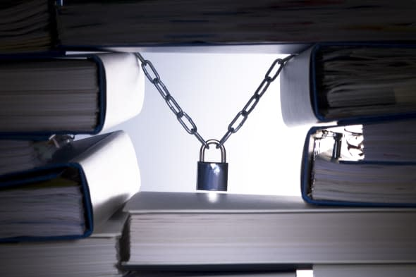 Stack of ringbinders holding up a padlock