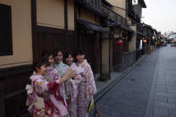 A group of Japanese women wearing kimono takes a selfie in the Gion district of Kyoto, Japan on March 18, 2020. Japanese tourism industry has taken a beating after Beijing banned group tours in late January. (AP Photo/Jae C. Hong)