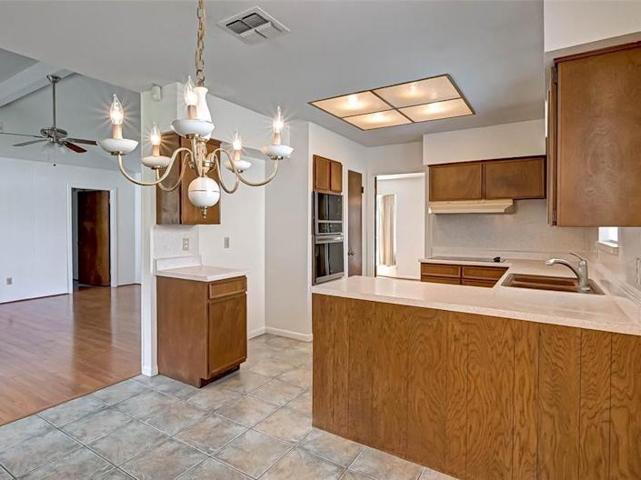 an outdated kitchen with wood cabinetry in a house for sale in houston