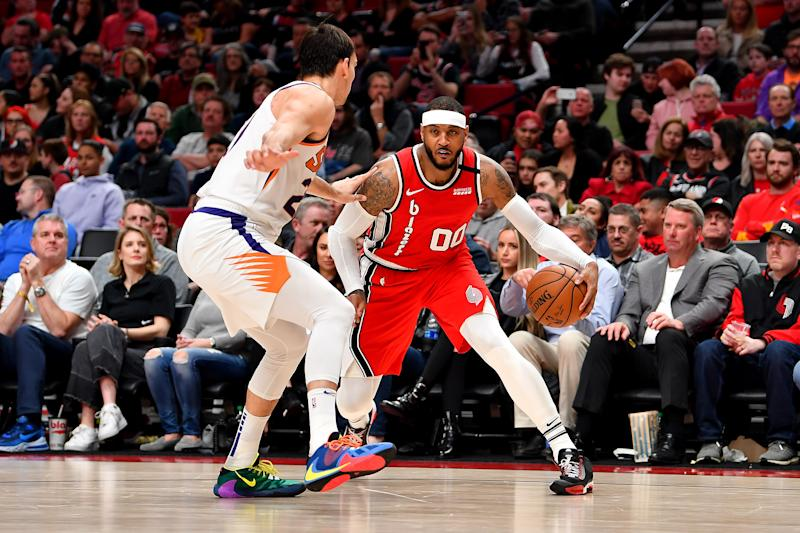PORTLAND, OREGON - MARCH 10: Carmelo Anthony #00 of the Portland Trail Blazers (R) moves the ball against Dario Saric #20 of the Phoenix Suns during the second half of the game at the Moda Center on March 10, 2020 in Portland, Oregon. The Portland Trail Blazers topped the Phoenix Suns, 121-105. NOTE TO USER: User expressly acknowledges and agrees that, by downloading and or using this photograph, User is consenting to the terms and conditions of the Getty Images License Agreement. (Photo by Alika Jenner/Getty Images)
