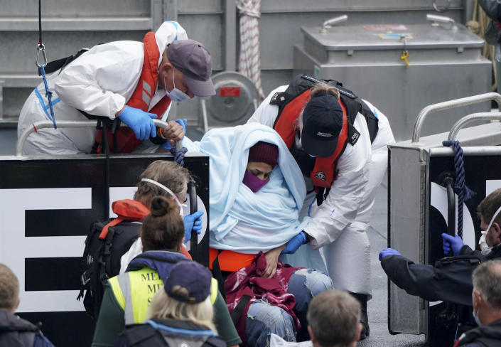 A woman is helped by Border Force officers as a group of people thought to be migrants are brought in to Dover, onboard a Border Force vessel, following a small boat incident in the Channel, in Kent, England, Monday July 26, 2021. (Gareth Fuller/PA via AP)