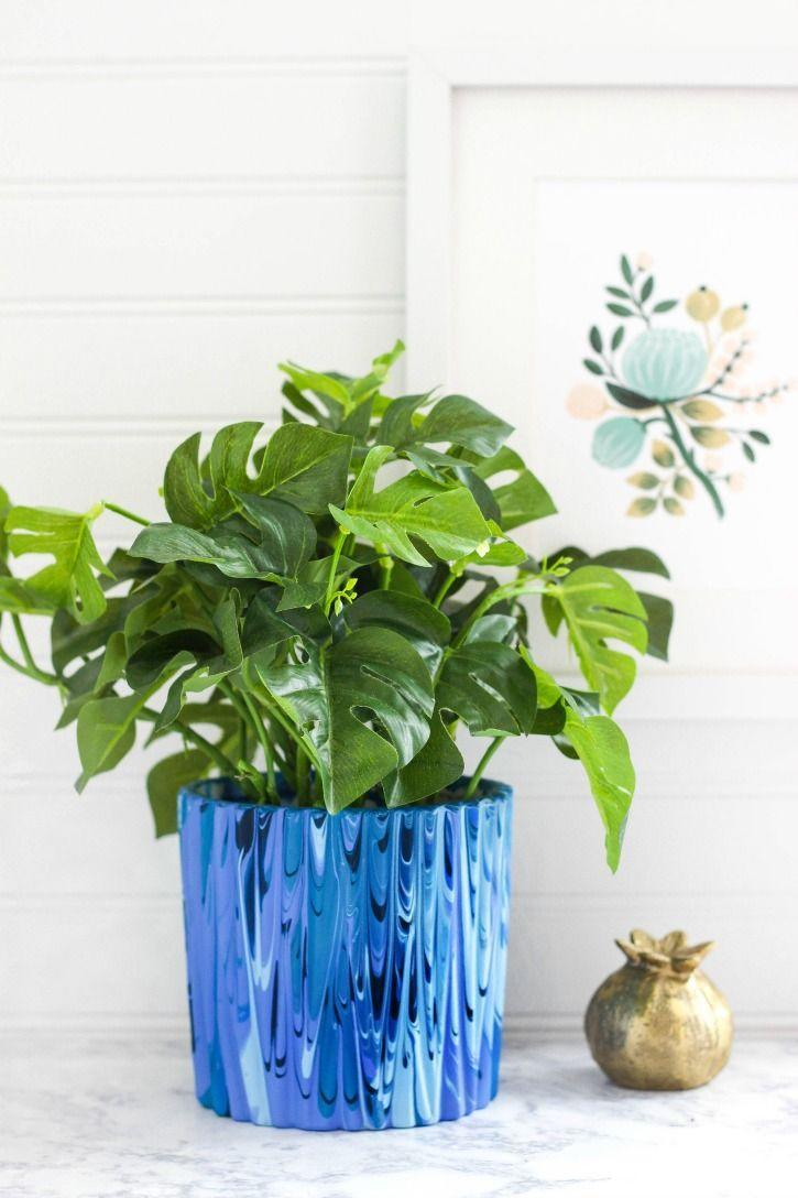"""<p>Poured paint is such a fun, mesmerizing technique to apply to a planter. You'll need a variety of paint colors, a ceramic planter, and disposable cups to achieve this look.</p><p><strong>Get the tutorial at <a href=""""https://www.purelykatie.com/poured-paint-planter/"""" rel=""""nofollow noopener"""" target=""""_blank"""" data-ylk=""""slk:Purely Katie"""" class=""""link rapid-noclick-resp"""">Purely Katie</a>.</strong></p><p><a class=""""link rapid-noclick-resp"""" href=""""https://go.redirectingat.com?id=74968X1596630&url=https%3A%2F%2Fwww.walmart.com%2Fsearch%2F%3Fquery%3Dacrylic%2Bpaint&sref=https%3A%2F%2Fwww.thepioneerwoman.com%2Fhome-lifestyle%2Fgardening%2Fg36556911%2Fdiy-planters%2F"""" rel=""""nofollow noopener"""" target=""""_blank"""" data-ylk=""""slk:SHOP ACRYLIC PAINT"""">SHOP ACRYLIC PAINT</a></p>"""