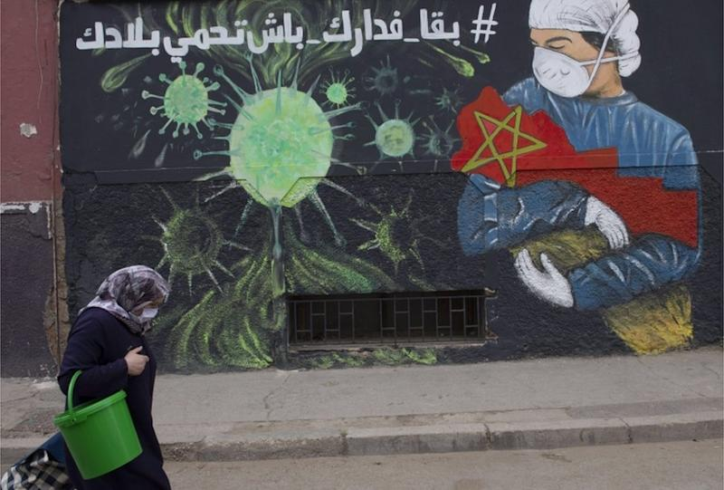A woman wearing a mask walks past a large mural depicting a masked health worker cradling the nation of Morocco in their arms.