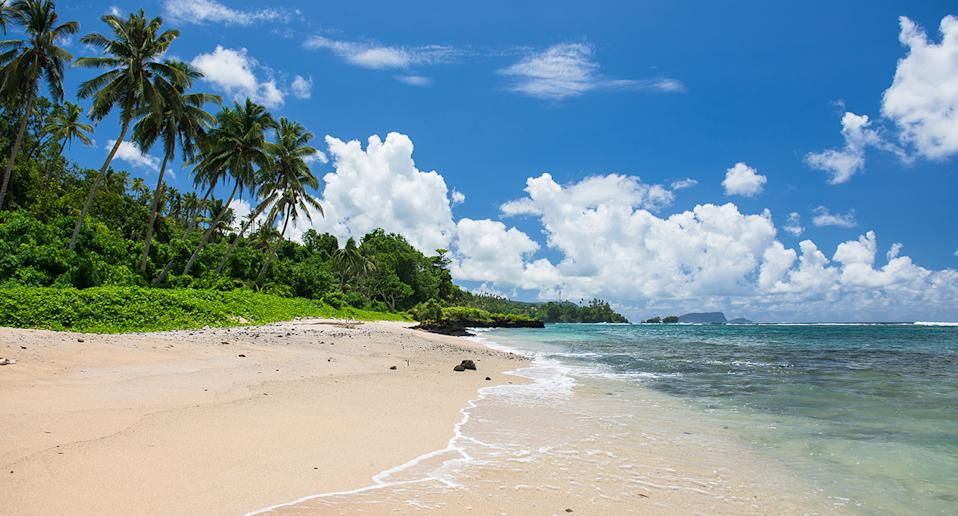 A landscape photo of a beach in Samoa, with blue skies and palm trees lining a sandy beach amd clear water.