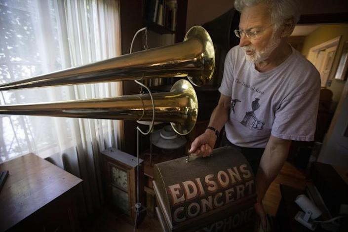 """SILVER LAKE, CALIF. - AUGUST 24, 2019: Collector John Levin of Silver Lake, Calif. show the Los Angeles Times some of his renowned wax cylinder at his home on Saturday, Aug. 24, 2019. According to Levin he is standing next to """"a 1900 double-horned phonograph used in the traveling media shows that were typical of the era. This machine easily filled a large tent with music."""" (Francine Orr / Los Angeles Times)"""