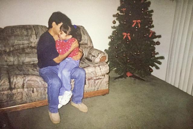 Karla Perez, as a child, with her dad at Christmastime.
