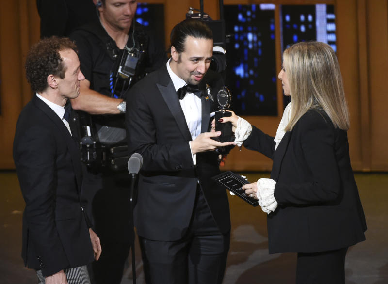 """FILE - In this June 12, 2016 file photo Barbra Streisand, right, presents the award for best musical to Lin-Manuel Miranda, center, of """"Hamilton,"""" as producer Jeffrey Seller looks on at the Tony Awards in New York. A filmed version of the original Broadway production will be available Friday, July 3, on Disney Plus. (Photo by Evan Agostini/Invision/AP, File)"""