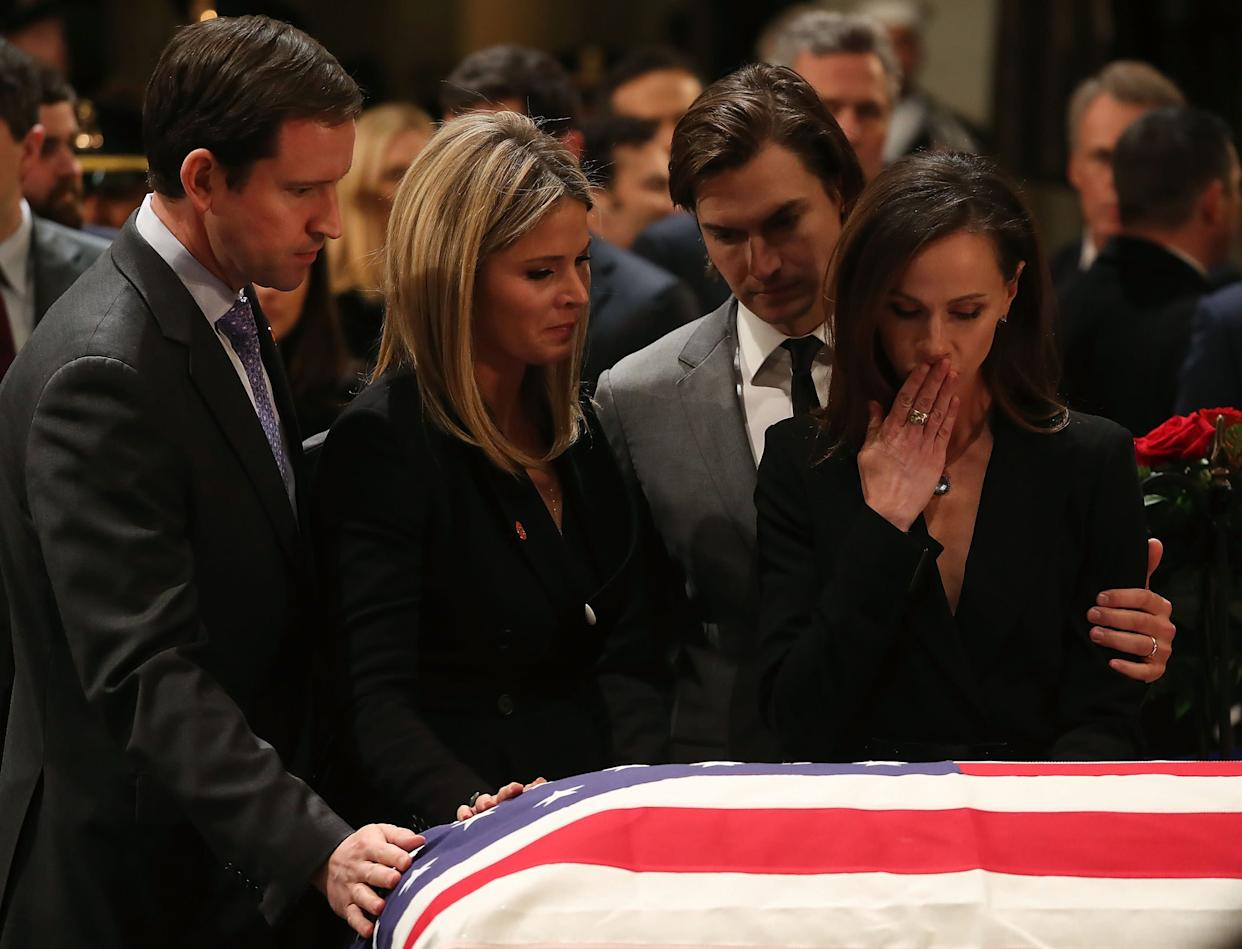 Jenna Bush Hager and her sister Barbara Bush stand with their husbands Henry Chase Hager, left, and Craig Coyne, second right, as they pay respect in front of the casket.